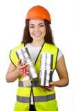 Muchacha en guardapolvos y un casco con las latas del metal y un cepillo en manos aislamiento Imagenes de archivo