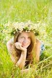 Muchacha en guirnalda de los camomiles en hierba Fotografía de archivo