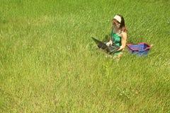 Muchacha en hierba con la computadora portátil Imagenes de archivo
