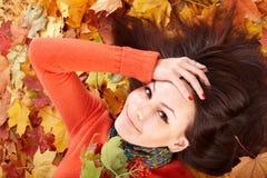 Muchacha en hojas anaranjadas del otoño. Imagen de archivo libre de regalías