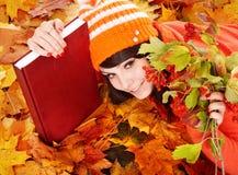 Muchacha en hojas de la naranja del otoño con el libro. Imágenes de archivo libres de regalías