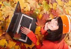 Muchacha en hojas de la naranja del otoño con la computadora portátil. Foto de archivo libre de regalías