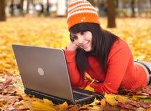 Muchacha en hojas de la naranja del otoño con la computadora portátil. Fotografía de archivo