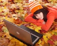 Muchacha en hojas de la naranja del otoño con la computadora portátil. Fotos de archivo libres de regalías