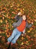 Muchacha en hojas de otoño fotografía de archivo