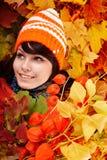 Muchacha en hojas de otoño con el manojo. Imágenes de archivo libres de regalías
