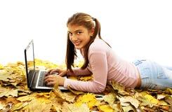 Muchacha en hojas de otoño con la computadora portátil Fotos de archivo libres de regalías