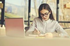 Muchacha en ideas del funcionamiento de vidrios las mejores al cuaderno antes de enviar al CEO vía correo electrónico usando el o imagen de archivo libre de regalías