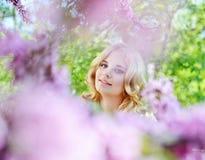 Muchacha en jardín de flores de la primavera Foto de archivo
