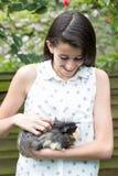 Muchacha en jardín que se ocupa el conejillo de Indias del animal doméstico Imágenes de archivo libres de regalías