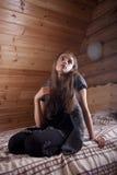 Muchacha en Jersey negra que se sienta en cama Fotografía de archivo