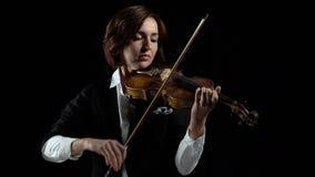 Muchacha en juego los violines en un cuarto Fondo negro metrajes