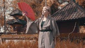 Muchacha en kimono con la fan roja de la mano