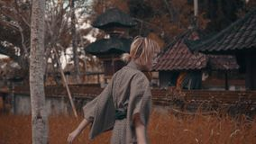 Muchacha en kimono con la fan roja de la mano almacen de video