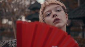 Muchacha en kimono con la fan roja de la mano metrajes