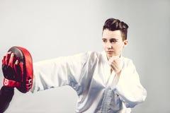 muchacha en kimono del traje del karate en estudio en el fondo gris El niño femenino muestra que los stans del judo o del karate  Fotografía de archivo