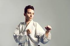 muchacha en kimono del traje del karate en estudio en el fondo gris El niño femenino muestra que los stans del judo o del karate  Imagen de archivo