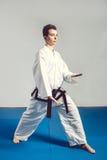 muchacha en kimono del traje del karate en estudio en el fondo gris El niño femenino muestra que los stans del judo o del karate  Foto de archivo