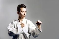 muchacha en kimono del traje del karate en estudio en el fondo gris El niño femenino muestra que los stans del judo o del karate  Fotos de archivo libres de regalías
