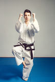muchacha en kimono del traje del karate en estudio en el fondo gris El niño femenino muestra que los stans del judo o del karate  Foto de archivo libre de regalías