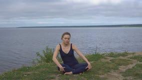 Muchacha en la actitud clásica de la yoga, concentración de la energía almacen de metraje de vídeo