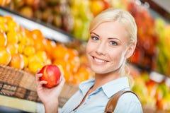 Muchacha en la alameda de compras que elige la manzana de manos de las frutas Imágenes de archivo libres de regalías