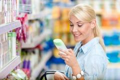 Muchacha en la alameda de compras que elige los cosméticos Imagen de archivo libre de regalías