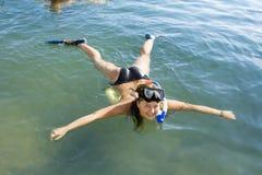 Muchacha en la aleta que miente en el mar Fotos de archivo libres de regalías