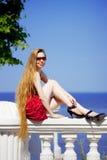 Muchacha en la alineada roja en la playa Foto de archivo
