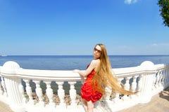 Muchacha en la alineada roja en la playa Foto de archivo libre de regalías