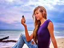 Muchacha en la arena cerca de la ayuda de la llamada del mar por el teléfono Imagenes de archivo