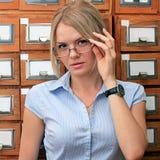 Muchacha en la biblioteca con la mirada de los vidrios Foto de archivo