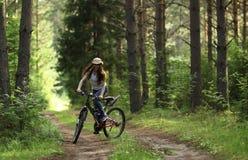 Muchacha en la bici en el bosque Foto de archivo