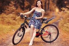 Muchacha en la bici en el bosque Foto de archivo libre de regalías