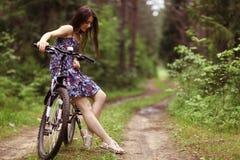 Muchacha en la bici en el bosque Imagen de archivo