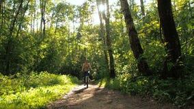Muchacha en la bicicleta en el parque Muchacha deportiva joven que completa un ciclo en el bosque metrajes