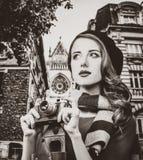 Muchacha en la boina y la bufanda que sostienen una cámara del vintage fotos de archivo