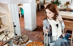 Muchacha en la bufanda que mira el caso de cristal de la panadería Imagenes de archivo