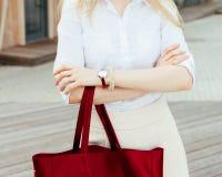 Muchacha en la calle con un bolso de moda estupendo rojo grande en una blusa y una falda blancas en una tarde caliente outdoor Fotografía de archivo libre de regalías