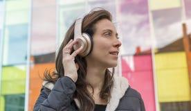 Muchacha en la calle que escucha la música con los auriculares en su hea Foto de archivo libre de regalías