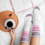 Muchacha en la cama con un libro viejo y una taza de café, visión superior Imagenes de archivo