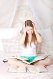 Muchacha en la cama, rodeada por los libros Fotografía de archivo libre de regalías