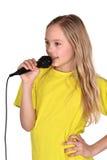 Muchacha en la camisa amarilla que canta Fotografía de archivo