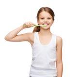 Muchacha en la camisa blanca en blanco que cepilla sus dientes Imágenes de archivo libres de regalías