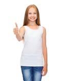 Muchacha en la camisa blanca en blanco que muestra los pulgares para arriba Imagenes de archivo
