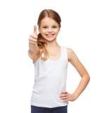 Muchacha en la camisa blanca en blanco que muestra los pulgares para arriba Foto de archivo libre de regalías