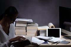 Muchacha en la camisa blanca que lee muchos libros de texto en la tabla con muchos hola Fotografía de archivo