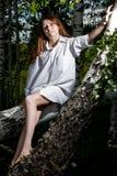 Muchacha en la camisa blanca que se sienta en el árbol Imágenes de archivo libres de regalías