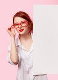 Muchacha en la camisa y los vidrios blancos con el tablero blanco Fotos de archivo libres de regalías