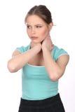 Muchacha en la camiseta azul que toca su cuello Cierre para arriba Fondo blanco Imagen de archivo libre de regalías
